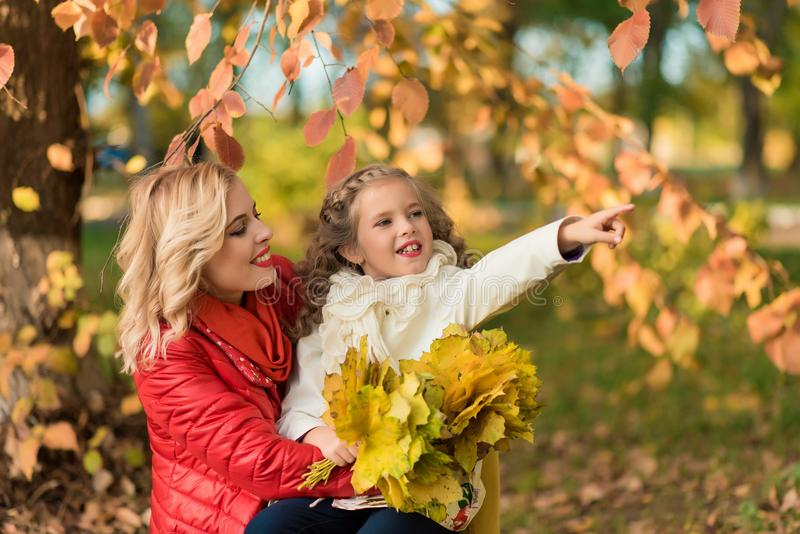 Happy joyful woman having fun with her girl in autumn color royalty free stock image