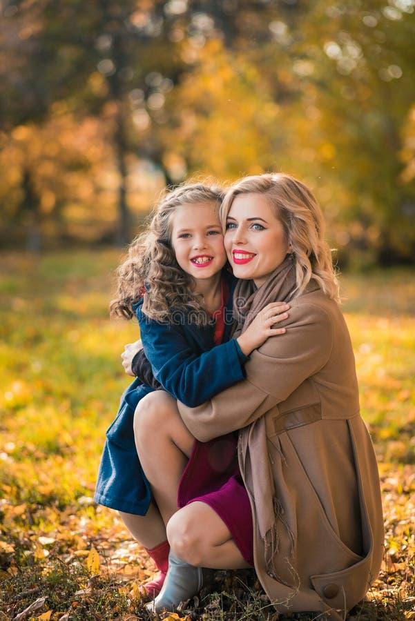 Happy joyful woman having fun with her girl in autumn color stock photos