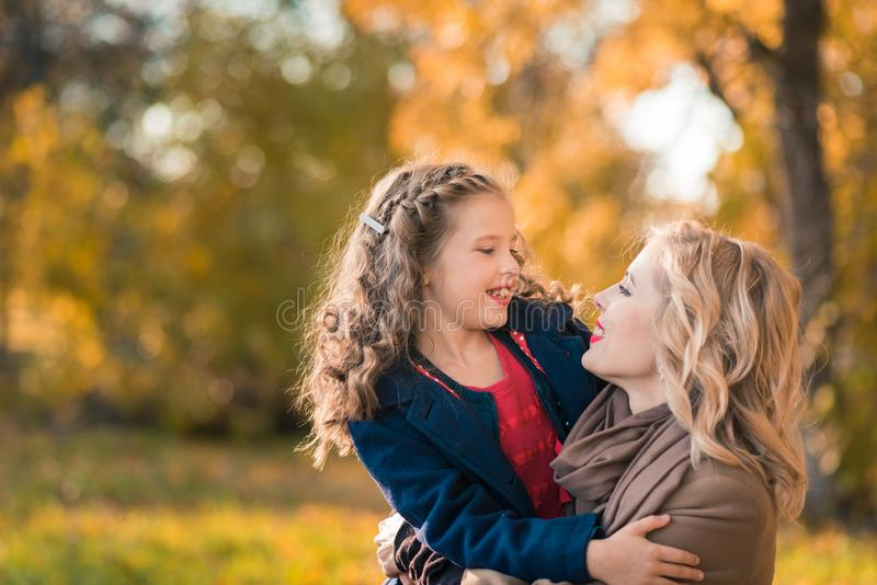 Happy joyful woman having fun with her girl in autumn color stock photography