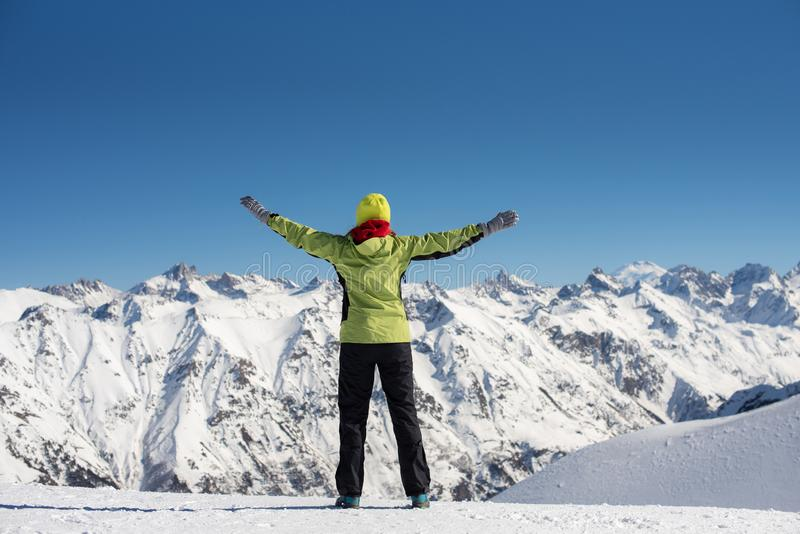 Happy joyful woman in ski suit having fun outdoors in winter, standing on the mountains covered with snow with raised up royalty free stock photography