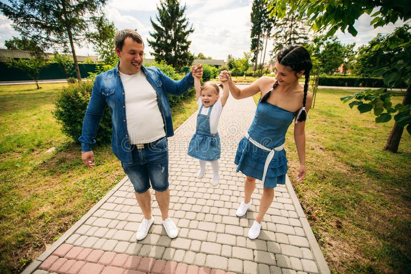 Happy joyful young family father, mother and little daughter having fun outdoors, playing together in summer park royalty free stock image