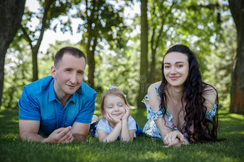 Happy joyful young family father, mother and little daughter having fun outdoors, playing together in summer park. Mom stock photography