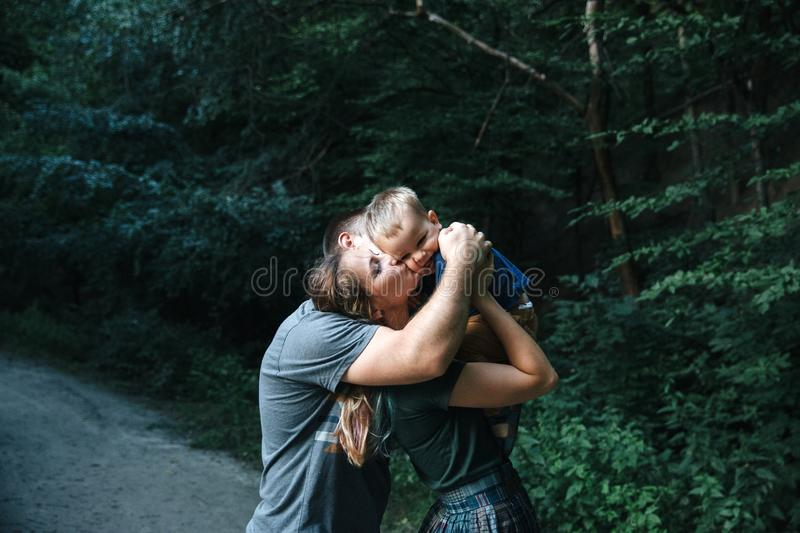 Happy joyful young family father, mother and little son having fun outdoors, playing together in summer park royalty free stock images