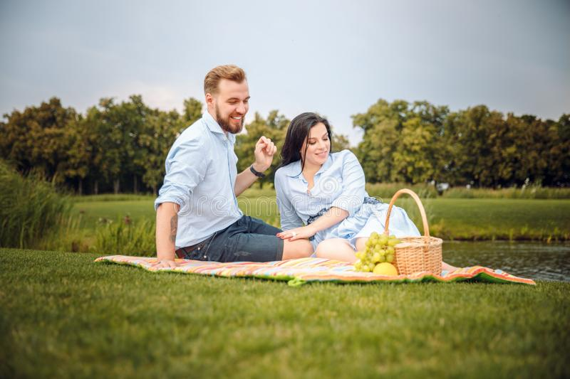 Happy joyful young family husband and his pregnant wife having fun together outdoors, at picnic in summer park stock image