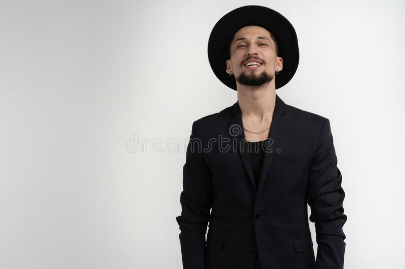Happy joyful young man with beard, wearing black trendy suit and hat smiling and looking at the camera isolated over royalty free stock photos