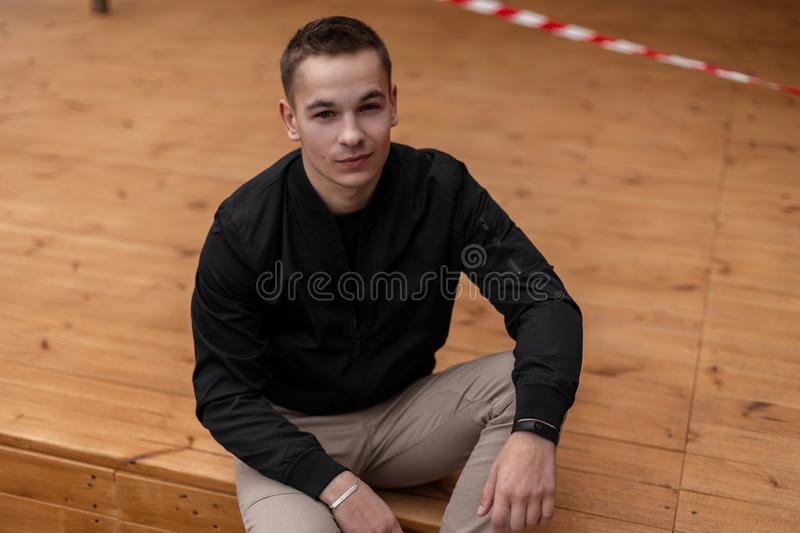 Happy joyful young man in fashionable clothes is sitting on a vintage wooden terrace outdoors in the warm spring day. stock photos