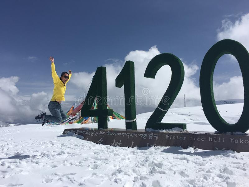 Happy jump in the highest pass of Qinghai Lake of China with altitude 4120 metres in snowy winter. My husband jumed beside the altitude mark with 4120 metres in stock images