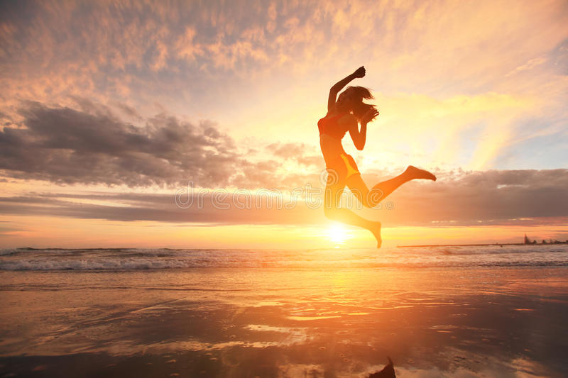 Happy jump sport woman. Happy jump sport young woman running on the beach at sunrise, asian royalty free stock photo