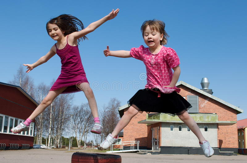 Happy jumping girls. On a blue sky background royalty free stock photo