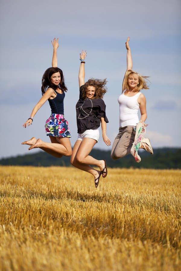 Happy jumping teenage girls royalty free stock photography