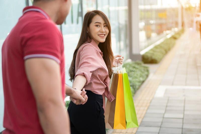 Happy Junge Shopper, die in der Einkaufsstraße spazieren gehen und farbenfrohe Einkaufstaschen in der Hand halten Die Frau drehte lizenzfreie stockfotos