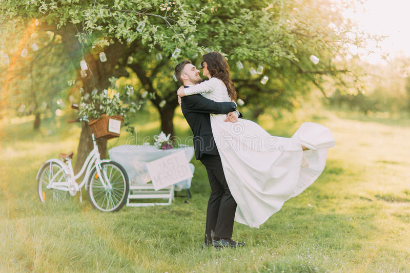Happy just married couple dancing on lawn in green sunny park. Bicycle near decorated tree at background stock image