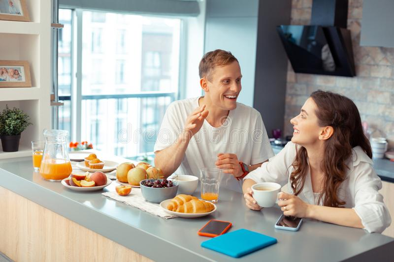Happy just married couple enjoying breakfast together stock images