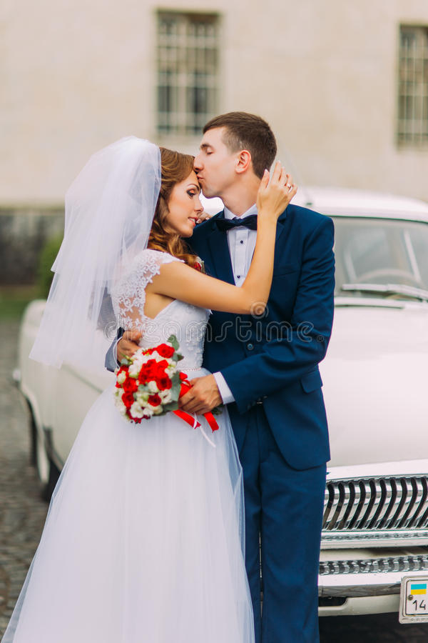 Happy just married couple holding each other in the background of vintage car royalty free stock photo