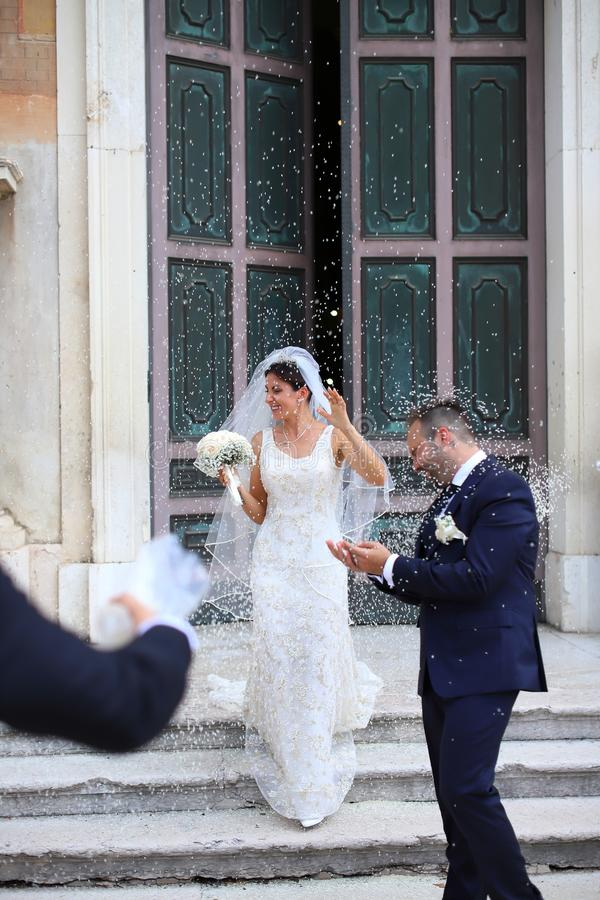 Happy just married couple under a rice rain. royalty free stock photography