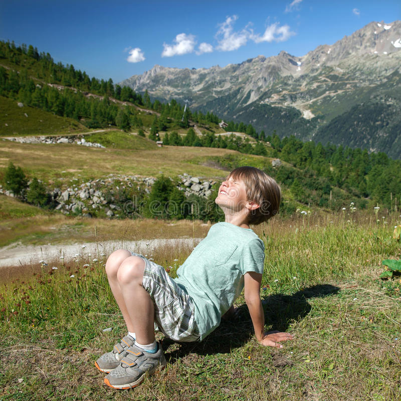 A happy kid is basking in sunlights. On a mountain slope royalty free stock photography