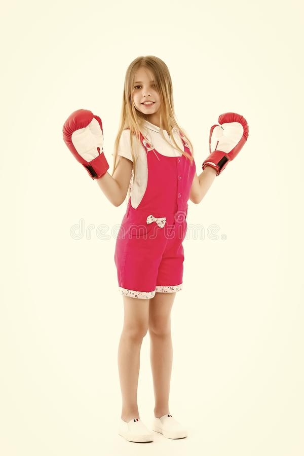 Happy kid in boxing gloves isolated on white. Little girl smile after boxing trainings. Punching. Childhood development. And health. Child boxer show power. I stock photography