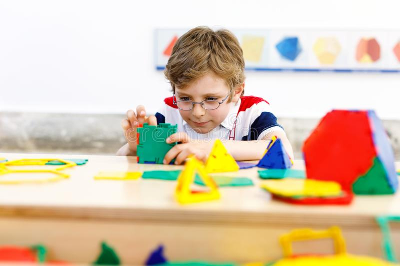 Happy kid boy with glasses having fun with building and creating geometric figures, learning mathematics and geometry. Little kid boy with glasses playing with stock images
