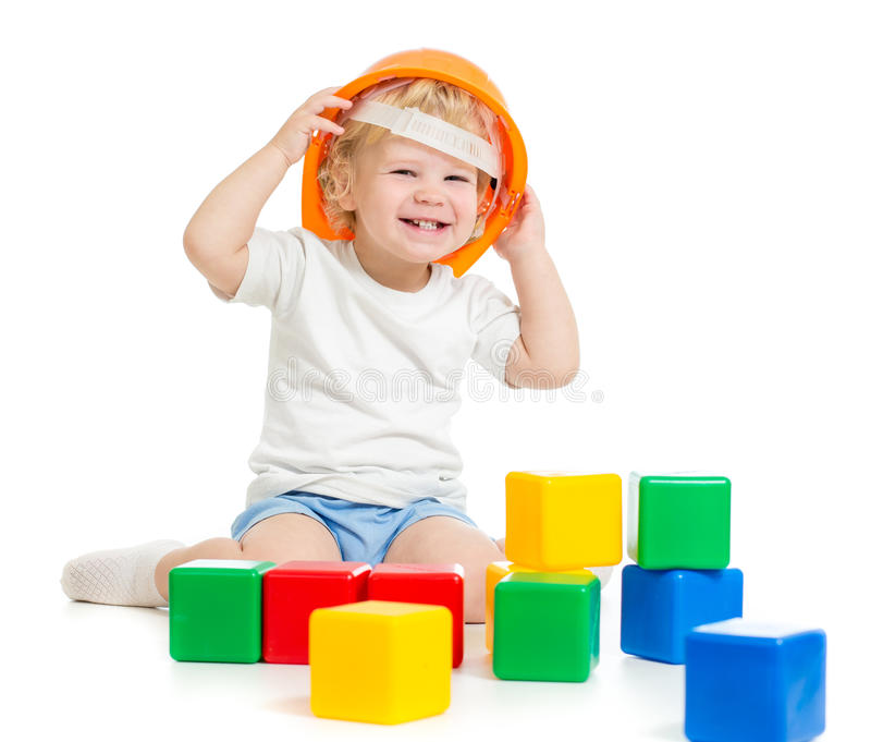 Happy kid boy in hard hat playing with colorful building blocks royalty free stock images