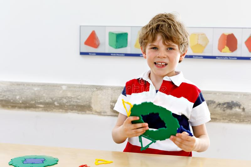 Happy kid boy having fun with building and creating geometric figures, learning mathematics and geometry. Little kid boy playing with lots of colorful plastic stock photography