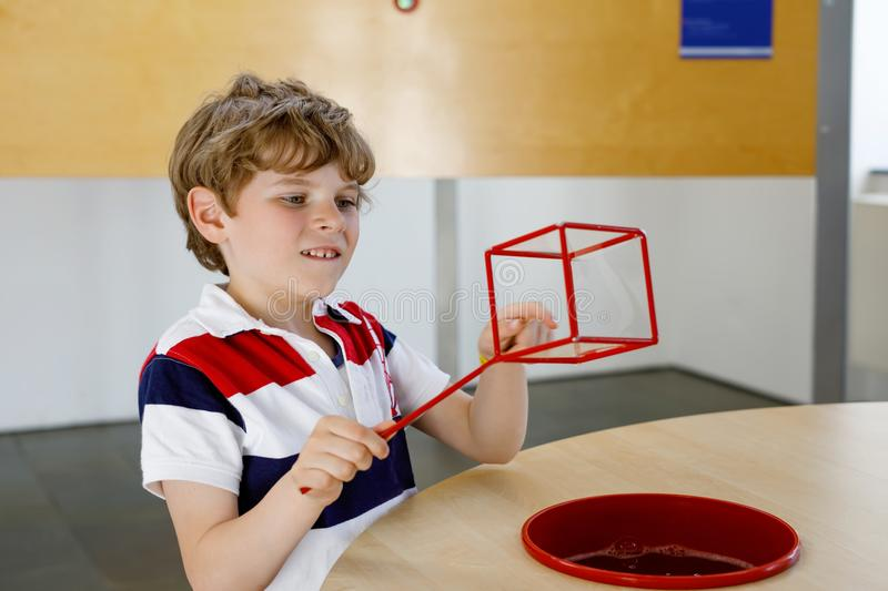 Happy kid boy having fun with building and creating geometric figures, learning mathematics and geometry. Little kid boy playing with lots of colorful plastic royalty free stock photo