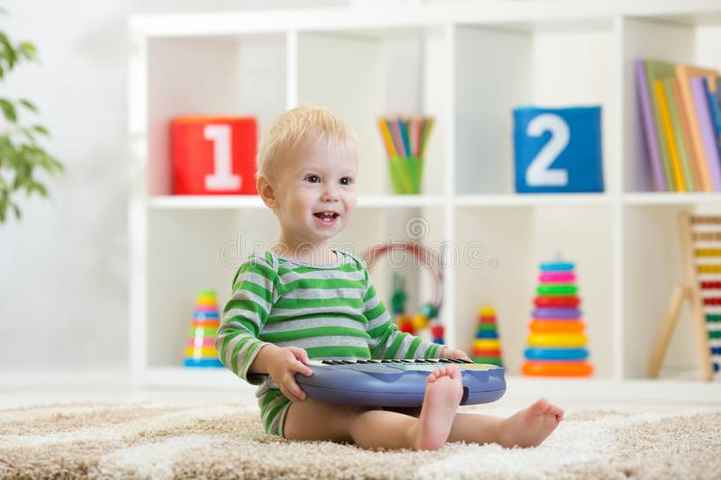 Happy kid boy playing piano toy in nursery room royalty free stock images