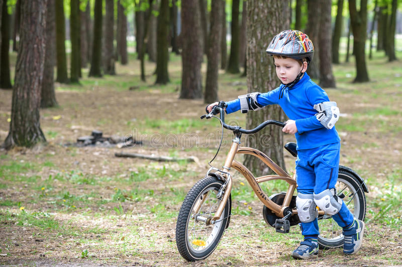 Happy kid boy of 4 years having fun in autumn forest with a bicycle on beautiful fall day. Active child making sports. Safety, lei royalty free stock photos