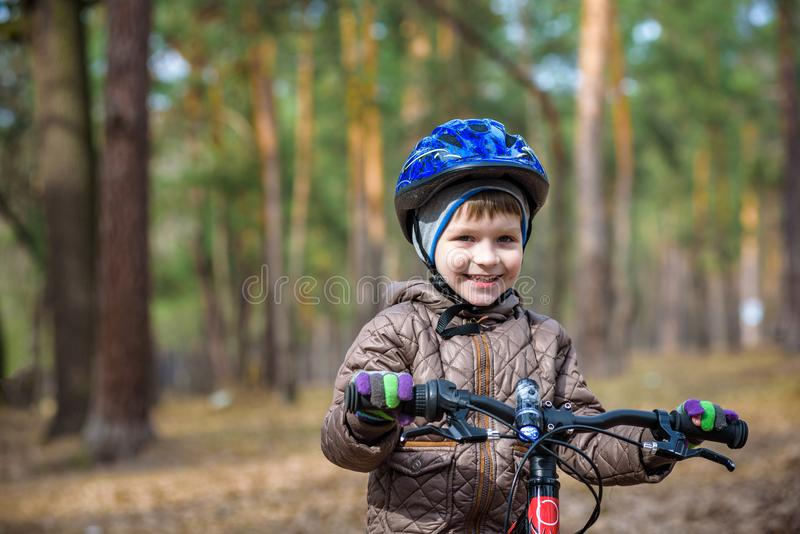 Happy kid boy of 3 or 5 years having fun in autumn forest with a bicycle on beautiful fall day. Active child wearing bike helmet. stock photography
