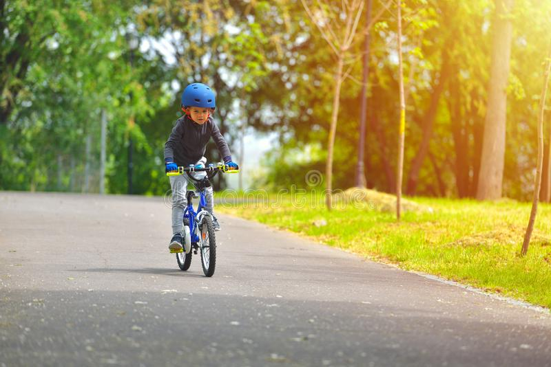 Happy kid boy of 5 years having fun in outdoor park with a bicycle on beautiful spring day. Active child making sports. Safety royalty free stock image