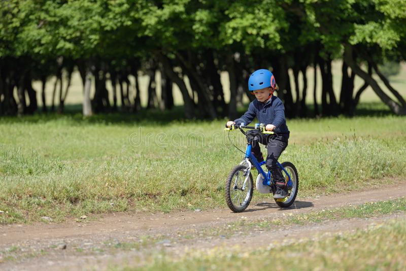 Happy kid boy of 5 years having fun in spring forest with a bicycle on beautiful fall day. Active child wearing bike helmet stock image