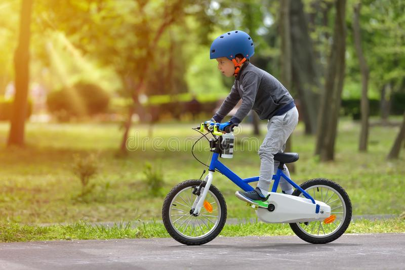 Happy kid boy of 5 years having fun in spring park with a bicycle on beautiful fall day. Active child wearing bike helmet stock photos