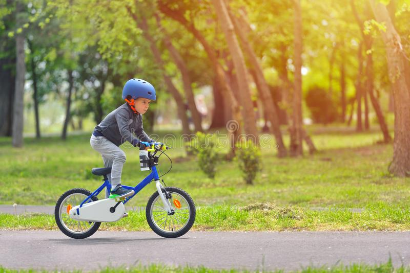 Happy kid boy of 5 years having fun in spring park with a bicycle on beautiful fall day. Active child wearing bike helmet stock images