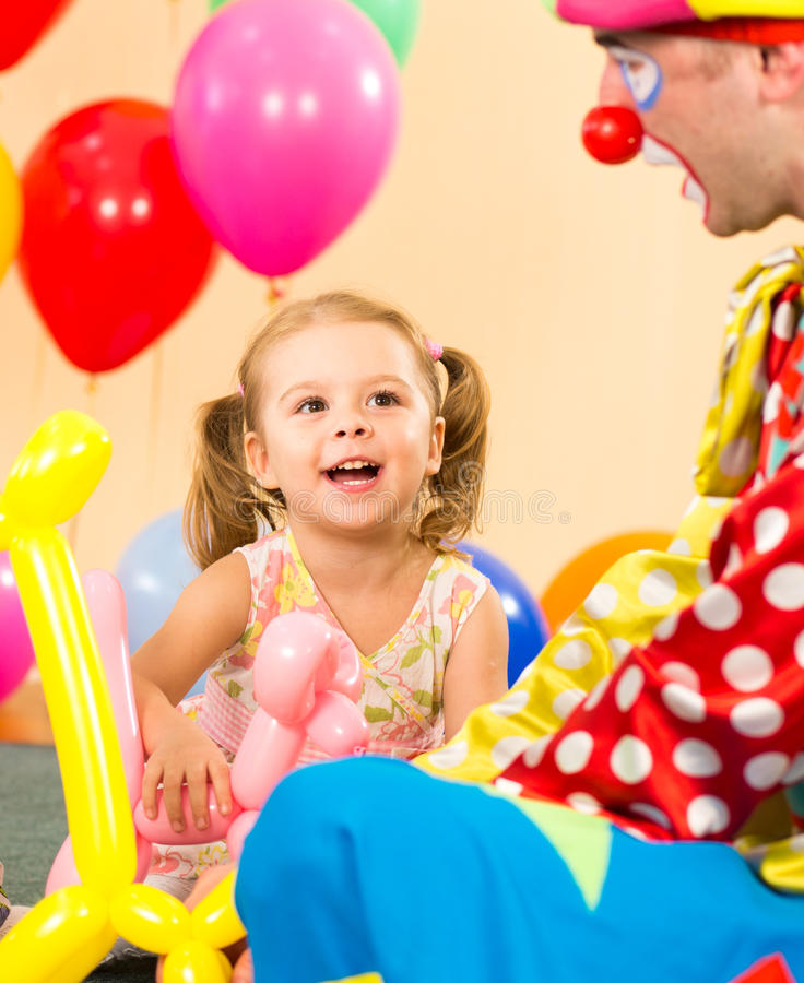 Happy kid and clown play on birthday party. Happy child girl and clown playing on birthday party royalty free stock photos