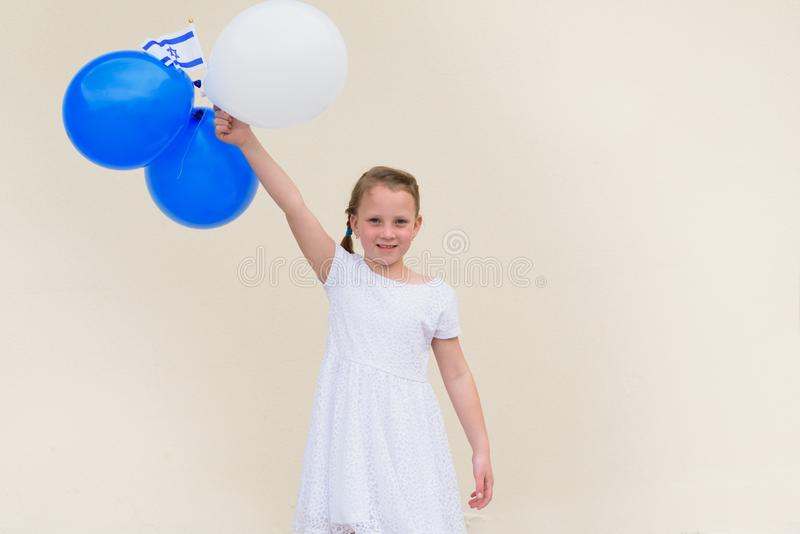 Happy little girl with blue and white balloons ans Israel flag. stock images