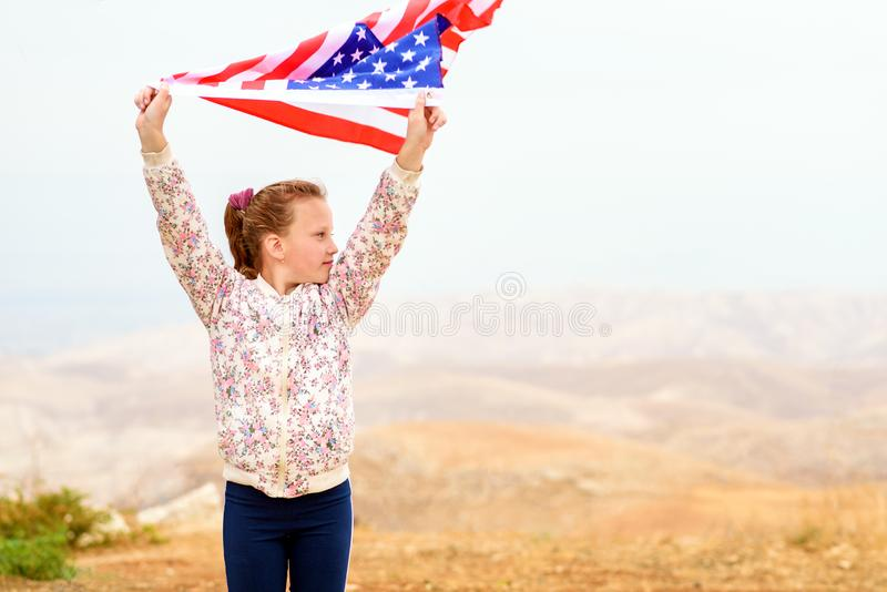 Little patriotic happy girl with american flag waving on nature outdoor background. USA celebrate 4th of July. royalty free stock images