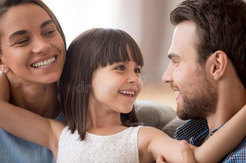 Happy kid daughter embracing parents looking at smiling mom royalty free stock images