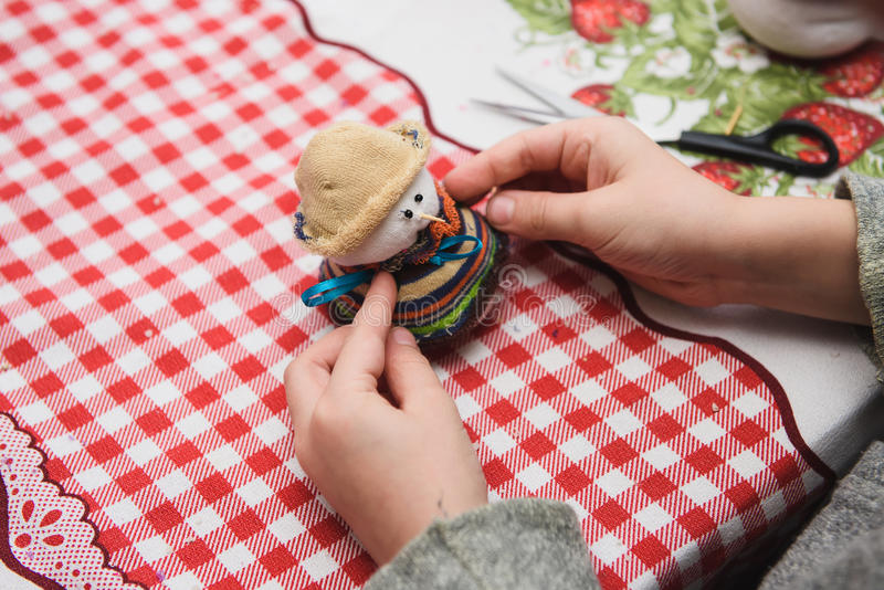Happy kid doing craft. Small child holding a felt Christmas snowman in hands. Workplace in kindergarten, school or home. Kids Christmas crafts idea. Children stock images