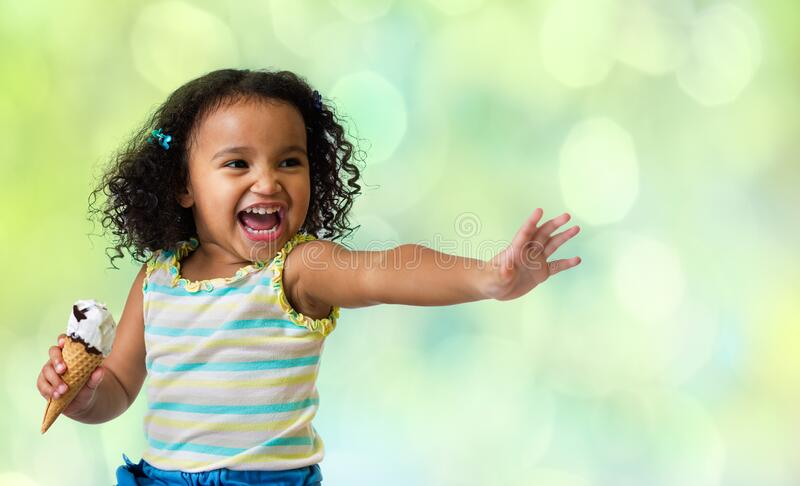 Happy kid eating ice cream on green abstract background stock images
