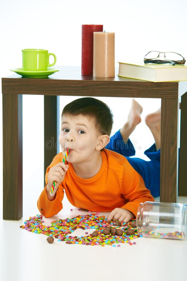Happy kid eating lollipop under table sweets spilt. Home indoor, isolated on white royalty free stock photos