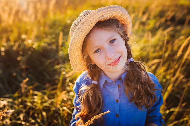 Happy kid girl in blue dress and straw walking on summer sunny meadow. royalty free stock images