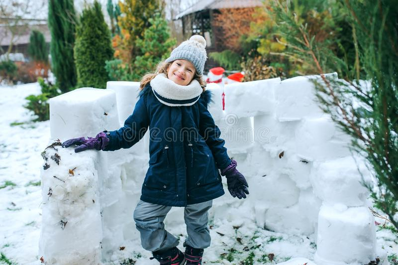 Happy kid girl building snow castle on winter holidays. Seasonal outdoor activities stock photos