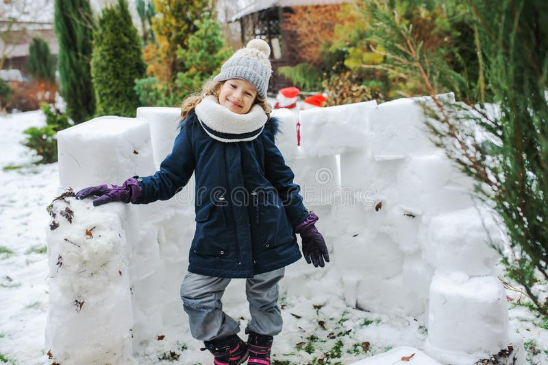 Happy kid girl building snow castle on winter holidays. Seasonal outdoor activities stock images