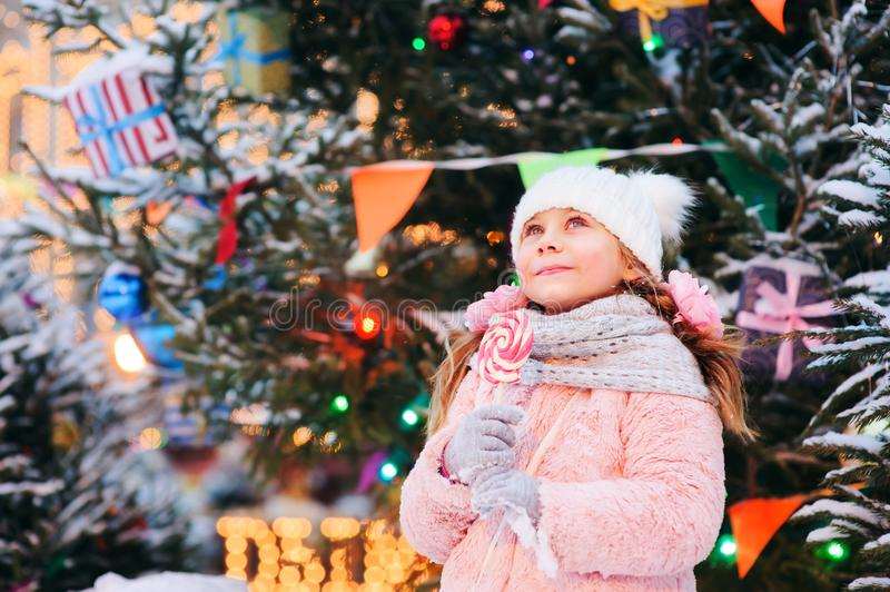 Happy kid girl with christmas candy. Winter holiday portrait at christmas tree stock photo