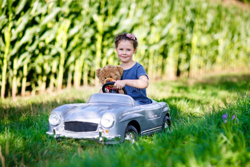 Happy kid girl driving big toy car and having fun with playing with big plush toy bear. Happy little kid girl driving big vintage old toy car and having fun with royalty free stock image