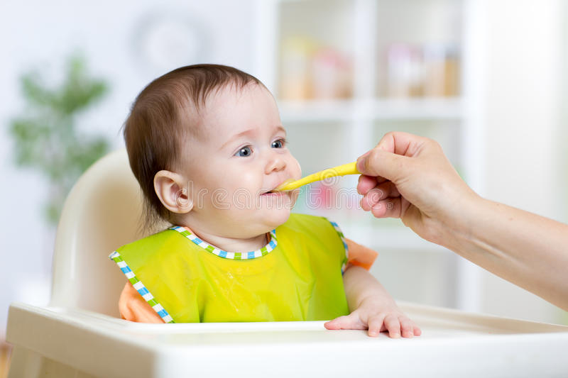 Happy kid girl eating food with spoon royalty free stock photos