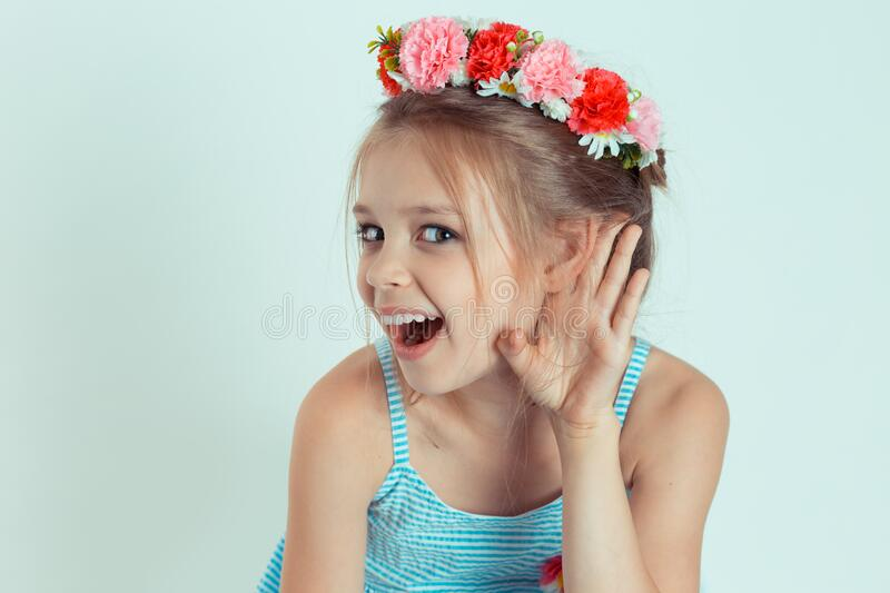Happy kid girl hand to ear eavesdropping trying to hear to a chipchat stock images