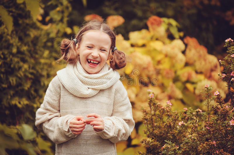 Happy kid girl playing in autumn garden near hydrangea bush with dried flowers stock photo