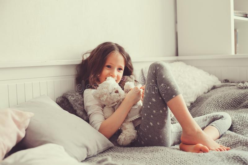 Happy kid girl playing with teddy bears in her room, sitting on bed. In pajama stock photo