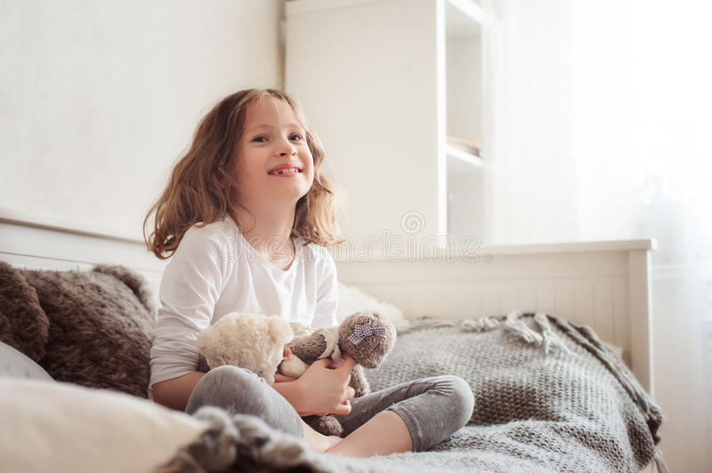 Happy kid girl playing with teddy bears in her room, sitting on bed. In the morning royalty free stock photos