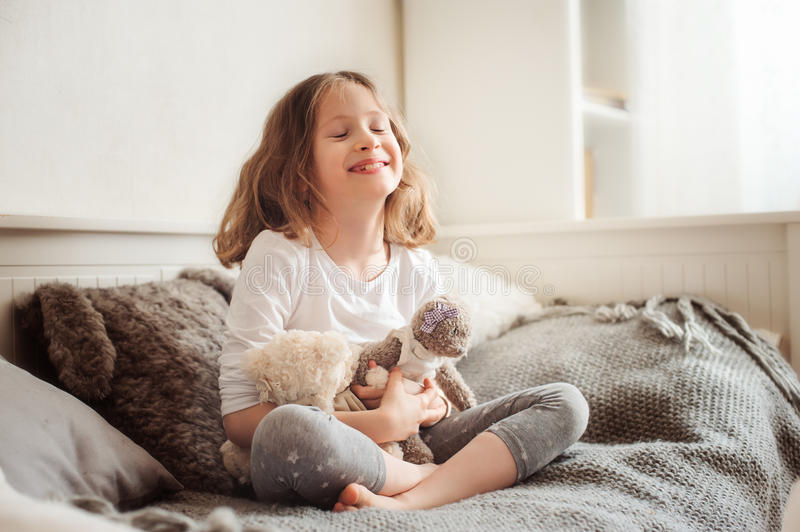 Happy kid girl playing with teddy bears in her room, sitting on bed. In the morning stock image